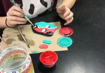 Photo depicting Drawing II student working on her Picasso styled ceramic face